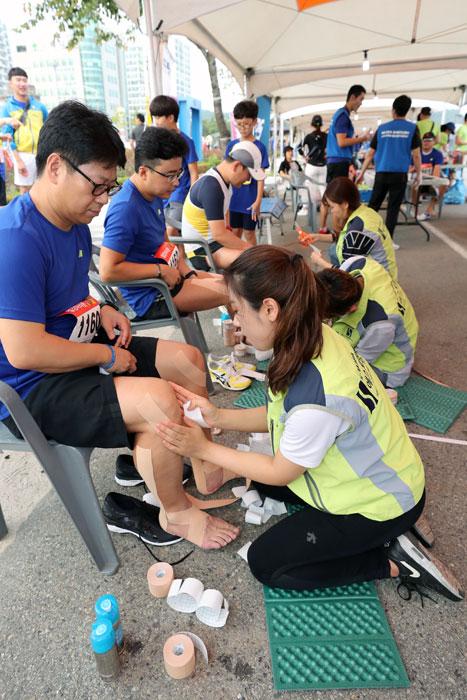 ▲ 에스포항병원 직원들이 참가자들에게 스포츠 테이핑 자원봉사를 하고 있다.