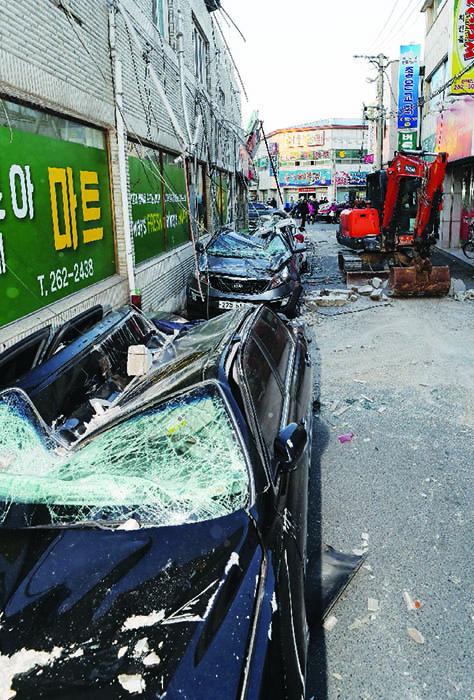 ▲ 지진의 충격으로 처참하게 파손된 건물 옆에 주차되있던 차량.