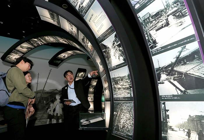 ▲ 오사카시에 있는 쓰나미·해일 스테이션의 관계자가 높은 파도 모형으로 만든 해일 피해터널에서 오사카를 덮쳤던 3대 태풍의 피해사진을 통해 당시의 상황을 전하고 있다.