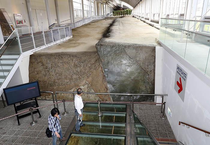▲ 시즈오카 시민인 타키다 아사에 부부가 '북단 지진재해 기념공원'에서 지진의 충격으로 솟아오른 단층의 모습을 보고 있다. 당시의 충격이 그대로 보존된 이 공원은 전체 길이가 140m에 이른다.
