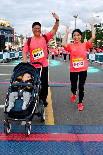 ▲ 아기와 함께 5km를 완주한 부부가 환한 표정으로 결승선을 통과하고 있다.
