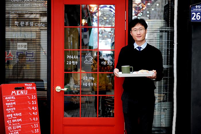 ▲ 안동시 옥야동 중앙신시장에서 '착한부엌' 커피점을 운영하는 권달우 대표가 주력 메뉴를 선보이며 환하게 웃고 있다.